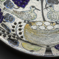 Birger Kaipiaisen maalaamassa keramiikkalautasessa kaksi lintua istuu linnunpesässä, jossa on kuusi munaa.  Suuret siniset marjatertut, orvokit ja keltaiset hedelmät ympäröivät lintuja.