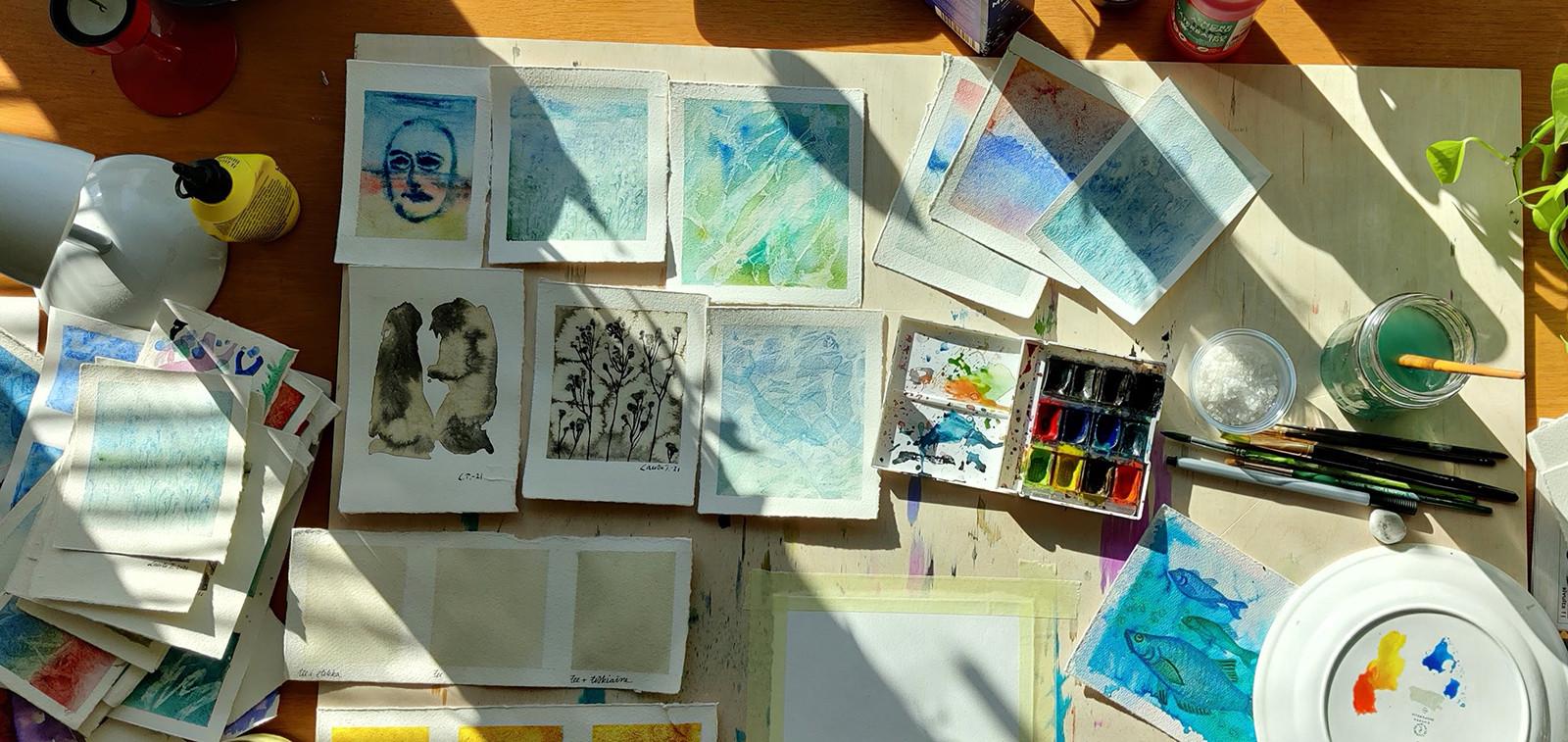 Akvarellimaalauksia pöydällä